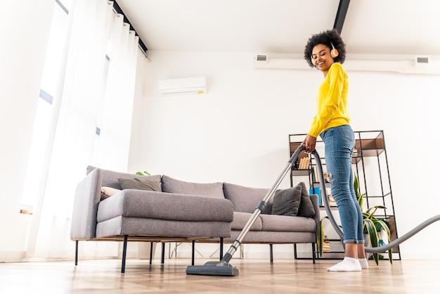 掃除機で家を掃除し、音楽を聴いて幸せな女性