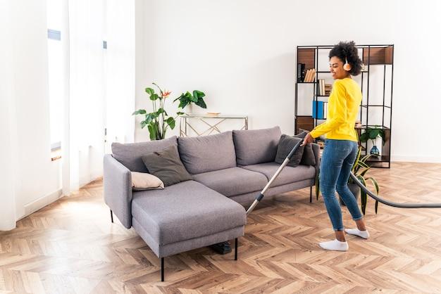 진공 청소기와 음악 듣기로 집을 청소하는 행복한 여성