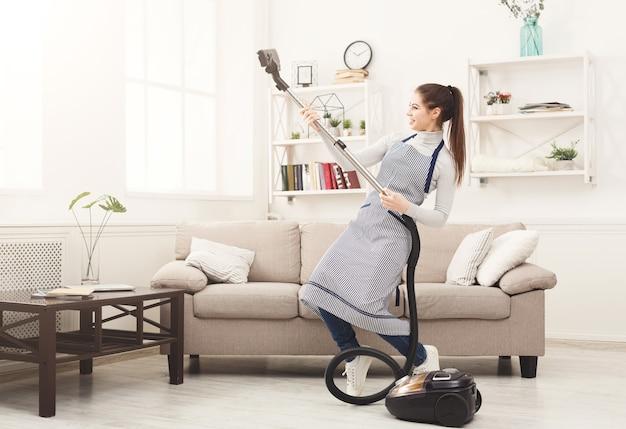 Счастливая женщина, уборка дома с пылесосом
