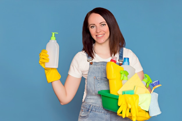 Happy woman cleaning lady with a bucket full of colorful detergent in rubber gloves,