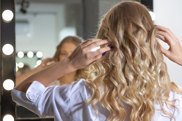 ビューティーサロンでヘアスタイリングした後、鏡で彼女の反射を見ている幸せな女性のクライアント