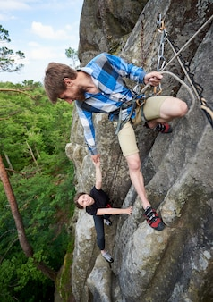 Happy woman climbing rock trekking outdoors. carefree hiker smiling her friend. friendly helping hand
