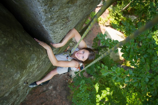 Happy woman climbing on a rocky wall rope, bouldering