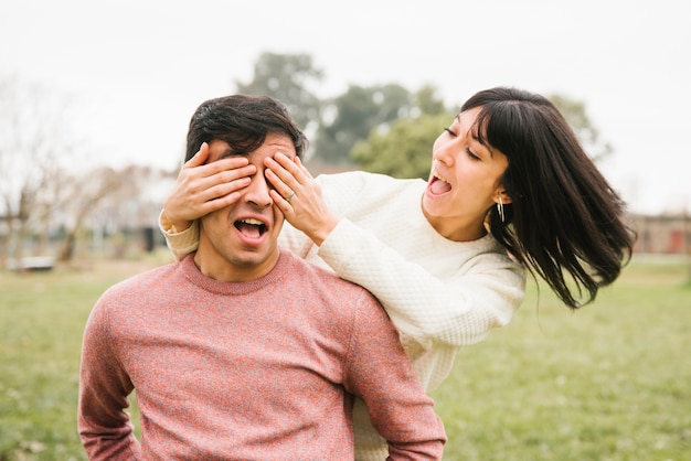Happy woman closing eyes of man with hands