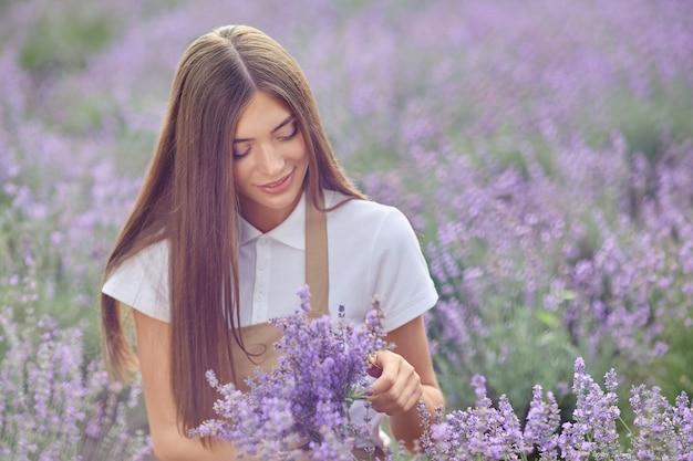 Donna felice che raccoglie fiori di lavanda in campo