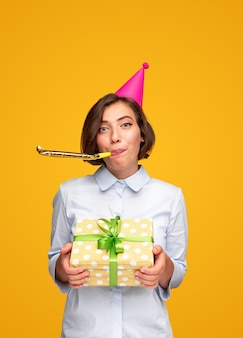 Happy woman congratulating on birthday giving present and blowing party horn looking at camera on yellow background