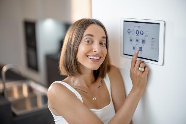 부엌에서 제어판을 사용하여 스마트 장치를 제어하는 행복한 여성