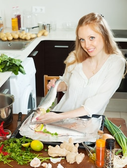 Happy woman cooking fish with lemon in sheet pan