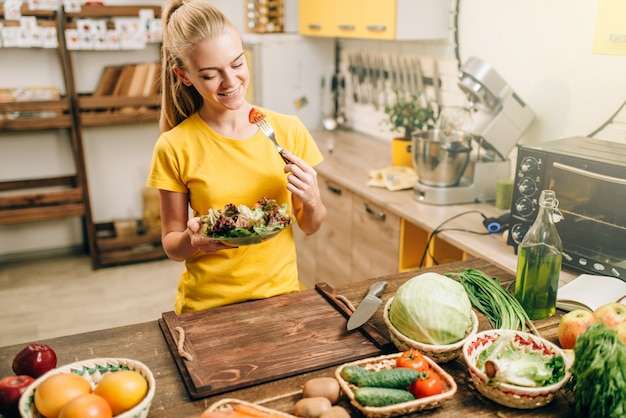 Happy woman cooking salad on the kitchen, healthy bio food preparing. vegetarian diet, fresh vegetables and fruits on wooden table