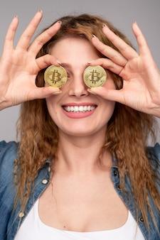 光沢のあるビットコインで目を覆う幸せな女性