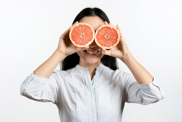 Happy woman covering her eyes with halved grape fruit against white backdrop