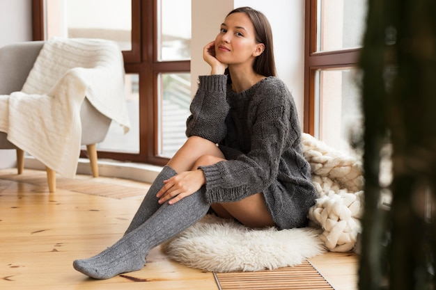 Happy woman in cozy clothes sitting on rug