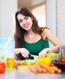 Happy  woman cutting vegetables
