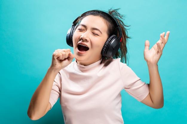 幸せな女性のダンスと音楽を聴く