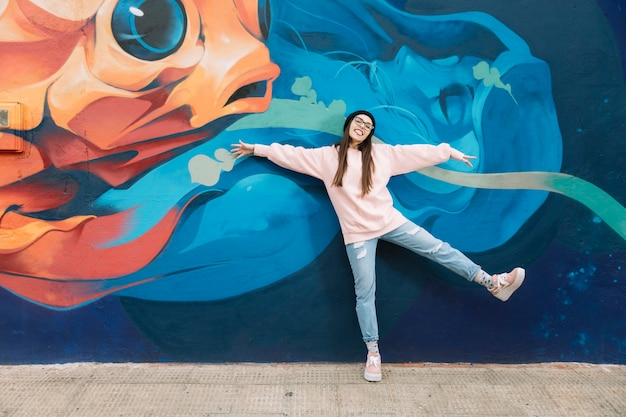 Happy woman dancing in front of colorful graffiti wall