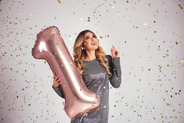 Donna felice che balla sotto la pioggia di coriandoli con un palloncino a forma di