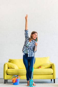 Happy woman dancing with mop at home