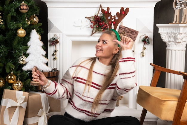 Happy woman in deer ears pointing at toy tree.