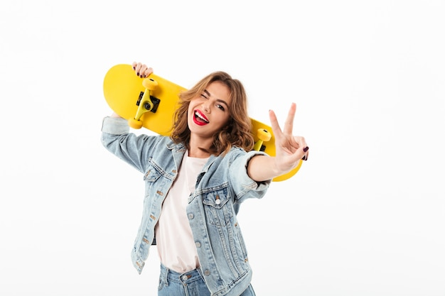 Happy woman in denim clothes with skateboard having fun  while winks and showing peace gesture over white wall