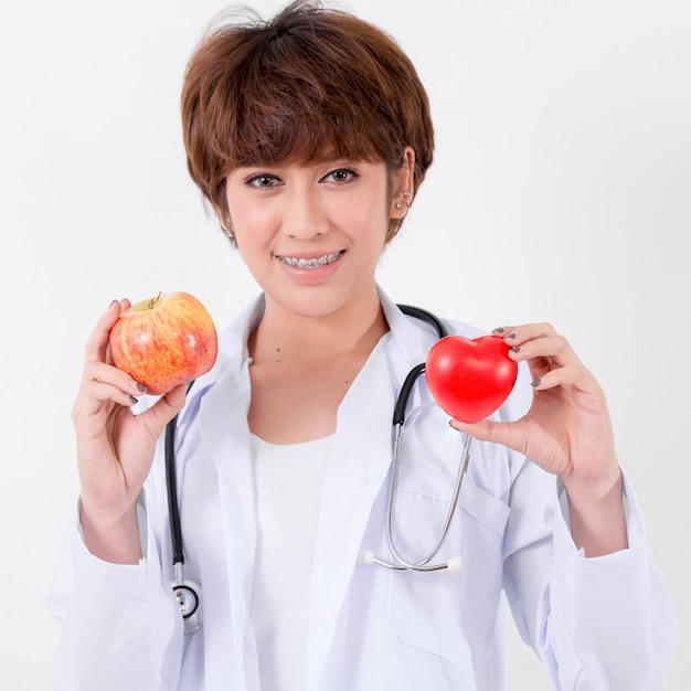 Happy woman doctor holding the red heart and apple