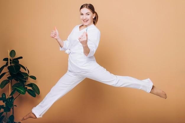 オレンジ色の背景に注射器でジャンプする白いスーツの幸せな女医師