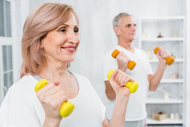 Happy woman doing exercise with dumbbells