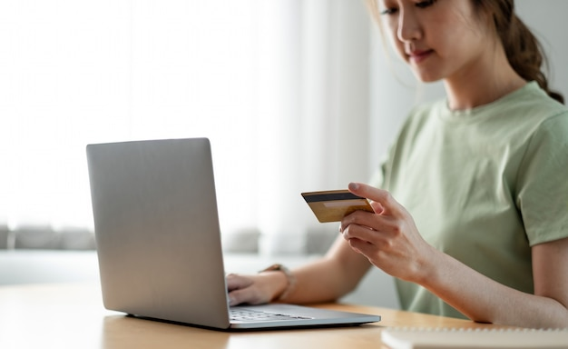 Счастливая женщина делает покупки в интернете дома, женщина рука кредитной карты и с помощью портативного компьютера.