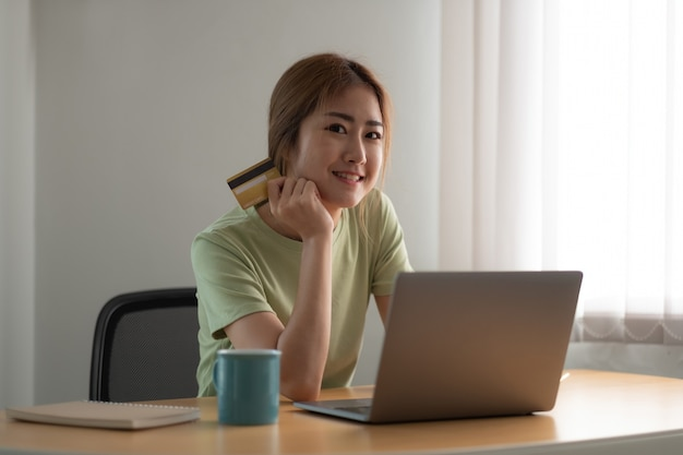 Happy woman doing online shopping at home, woman hand holding credit card and using laptop computer.