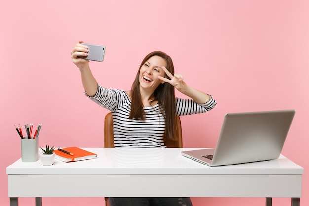Happy woman doing taking selfie shot on mobile phone showing victory sign while sit and work at white desk with pc laptop