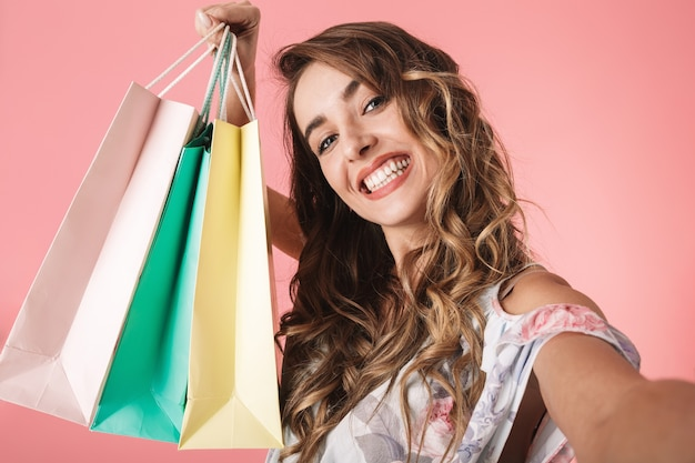 Happy woman in dress holding colorful shopping bags and taking selfie, isolated on pink