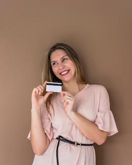 Happy woman in dress standing with credit card