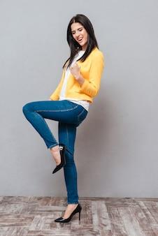 黄色のジャケットに身を包んだ幸せな女性は、灰色の表面上で勝者のジェスチャーをします。下を見下ろす。