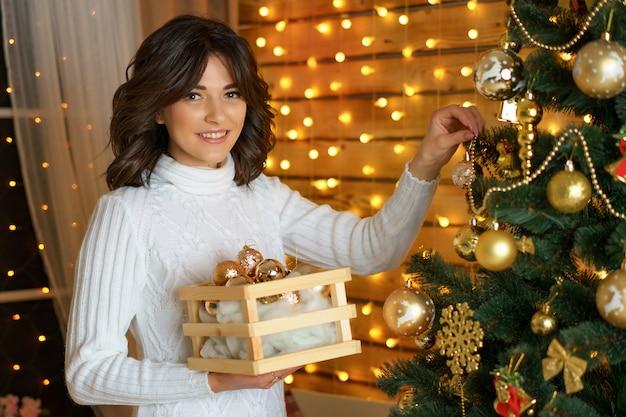 Happy woman dresses up a festive christmas tree, hangs balls