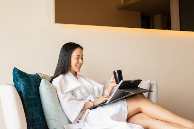 Happy woman in dressing gown sit on couch holding coffee working on laptop.