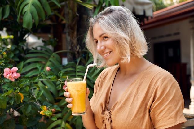 Happy woman drink экзотический желтый коктейль смузи