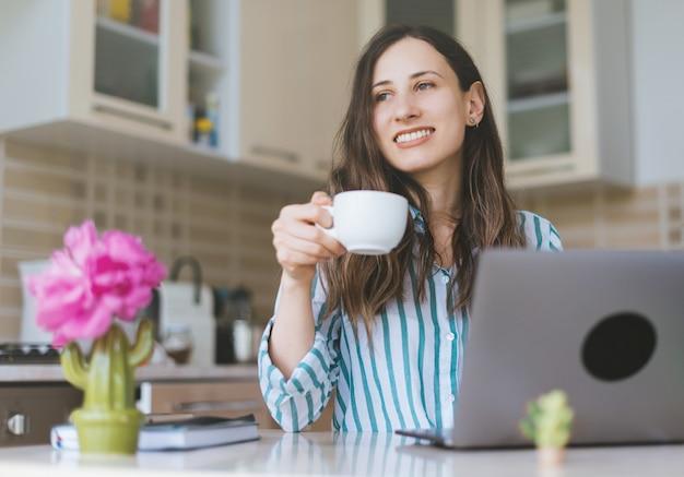Счастливая женщина пьет утренний чай или кофе на кухне, работая из дома