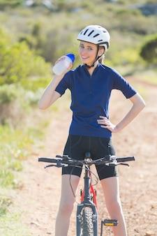 自転車に乗って幸せな女性を飲む
