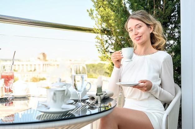 Счастливая женщина пьет кофе за завтраком на террасе
