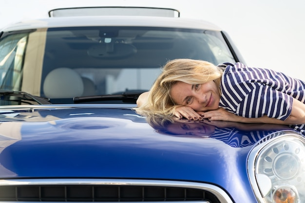 Happy woman driver embracing hood of car after detailing polishing car insurance advertisement