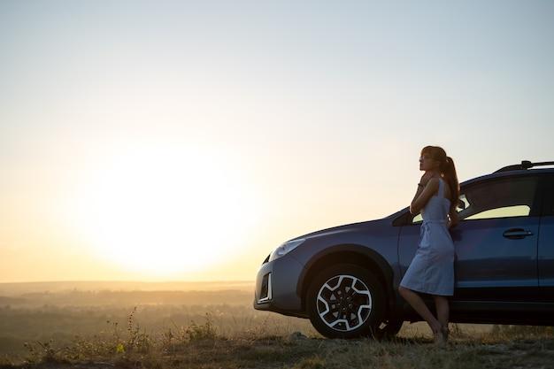 Счастливая женщина-водитель в голубом летнем платье, наслаждаясь теплым вечером возле своей машины. концепция путешествий и каникул.