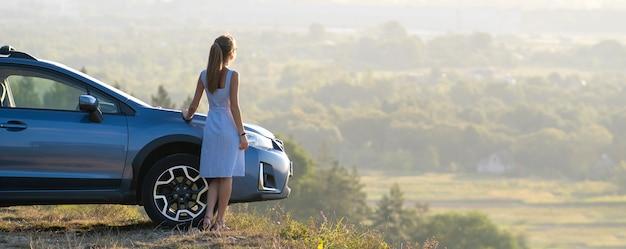 彼女の車の近くで暖かい夜を楽しんでいる青い夏のドレスで幸せな女性ドライバー。旅行と休暇のコンセプト。