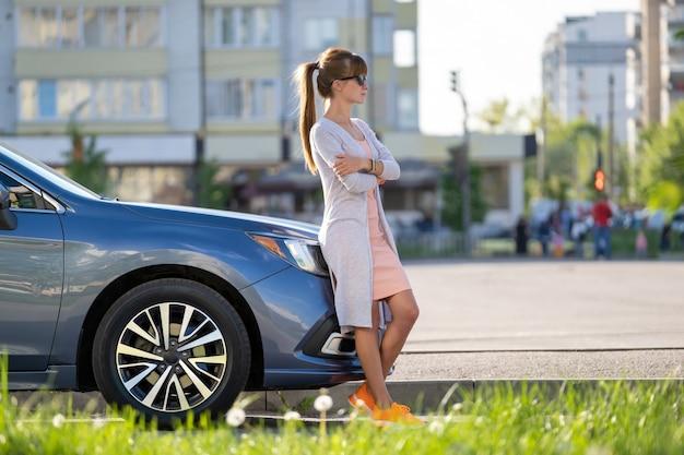 夏の通りで彼女の車の近くで暖かい日を楽しんでいるカジュアルな服装で幸せな女性ドライバー