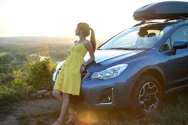 彼女の車の近くで暖かい夜を楽しんで夏のドレスで幸せな女性ドライバー。旅行と休暇のコンセプト。