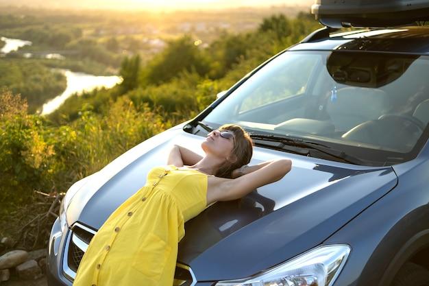 Счастливая женщина-водитель в летнем платье, наслаждаясь теплым вечером возле своей машины
