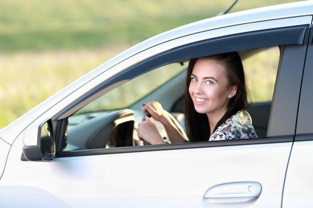 그녀의 새 차를 운전하는 행복 한 여자