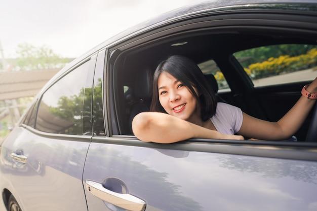 彼女の新しい車を運転して幸せな女