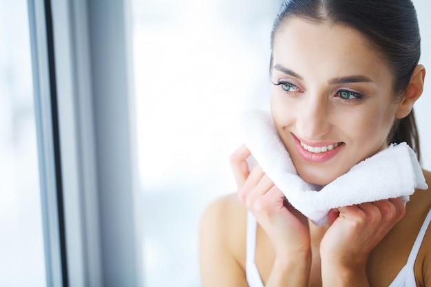 幸せな女タオルで肌を乾燥