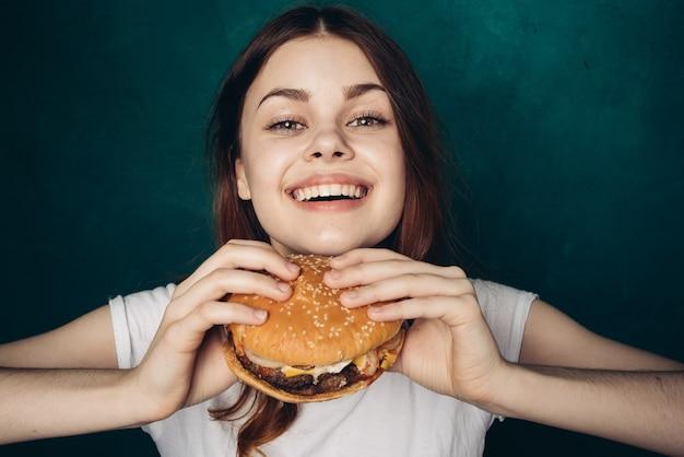 Счастливая женщина ест гамбургер, студия