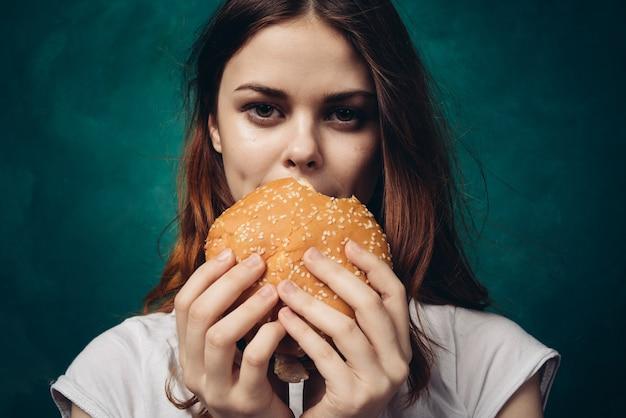 Счастливая женщина ест гамбургер