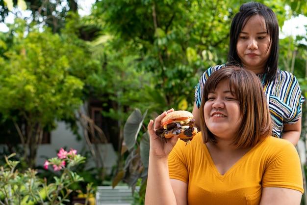 과체중 여자는 휠체어에 있고 햄버거를 먹지만 친구는 행복하지 않습니다.